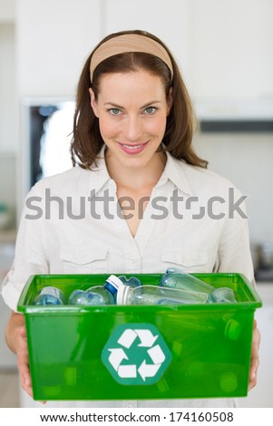 Portrait of a smiling young woman carrying box with recycling symbol in the house