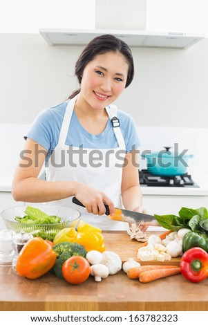 Portrait of a smiling young woman chopping vegetables in the kitchen at home