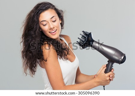 Portrait of a smiling young woman dries her hair over gray background - stock photo