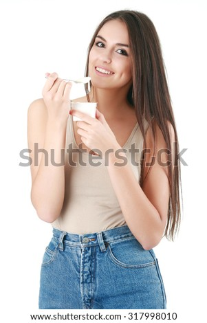 Portrait of a smiling young woman eating yogurt isolated - stock photo