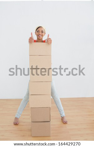Portrait of a smiling young woman gesturing thumbs up with stack of boxes in a new house