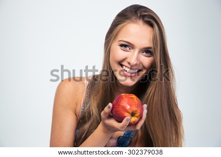 Portrait of a smiling young woman holding apple isolated on a white background. Looking at camera - stock photo
