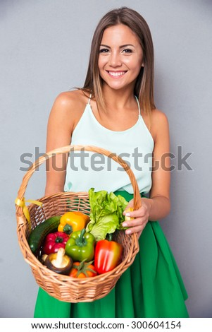 Portrait of a smiling young woman holding basket with vegetables over gray background - stock photo