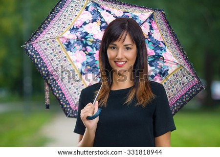 Portrait of a smiling young woman holding umbrella and looking at camera - stock photo