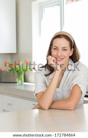Portrait of a smiling young woman in the kitchen at home - stock photo