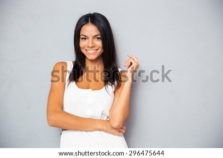 Portrait of a smiling young woman looking at camera over gray background - stock photo