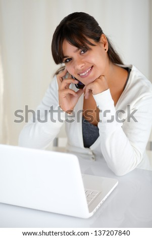 Portrait of a smiling young woman looking at you in front of laptop while is speaking on cellphone