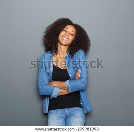 Portrait of a smiling young woman posing with arms crossed on gray background - stock photo