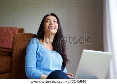 Portrait of a smiling young woman relaxing at home with a laptop - stock photo