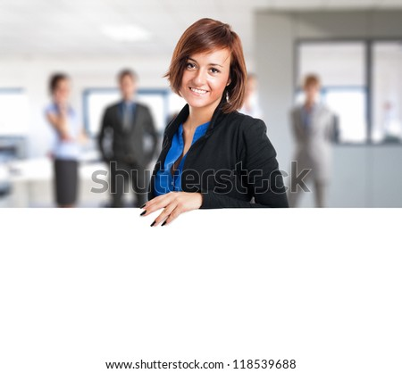 Portrait of a smiling young woman showing a blank board - stock photo