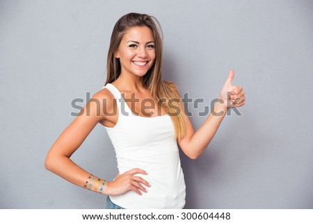 Portrait of a smiling young woman showing thumb up over gray background. Looking at camera - stock photo