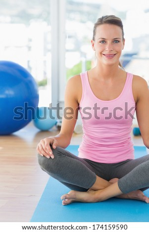 Portrait of a smiling young woman sitting at a bright fitness studio