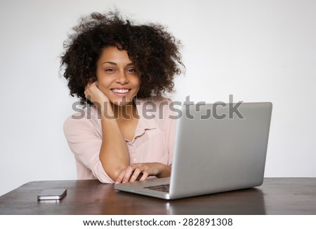 Portrait of a smiling young woman sitting at table with laptop - stock photo