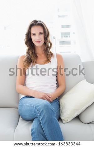 Portrait of a smiling young woman sitting on sofa in living room at home