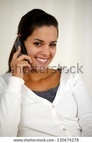 Portrait of a smiling young woman speaking on cellphone while is looking at you