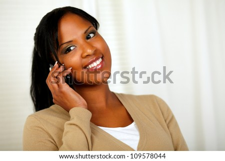 Portrait of a smiling young woman talking on cellphone at soft colors composition - stock photo