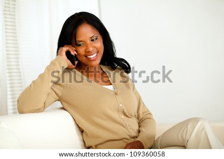 Portrait of a smiling young woman talking on cellphone while sitting on sofa at home indoor - stock photo