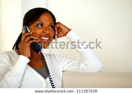 Portrait of a smiling young woman talking on phone at home indoor while looking up. With copyspace