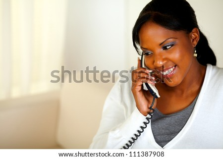 Portrait of a smiling young woman talking on phone. With copyspace