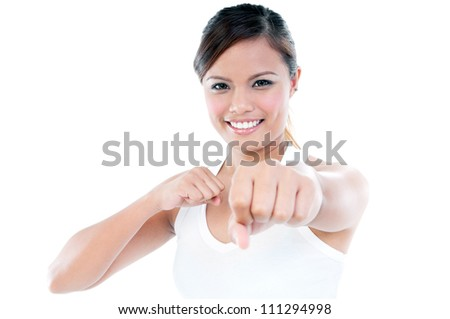Portrait of a smiling young woman throwing a punch, isolated on white.