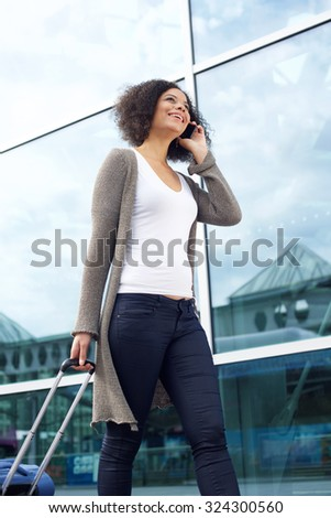 Portrait of a smiling young woman traveling with bag and mobile phone - stock photo