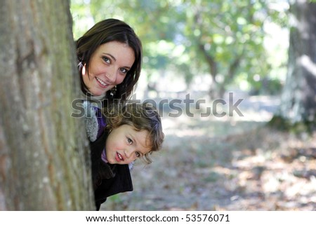 Portrait of a smiling young woman with a little girl - stock photo