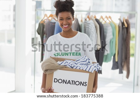 Portrait of a smiling young woman with clothes donation - stock photo