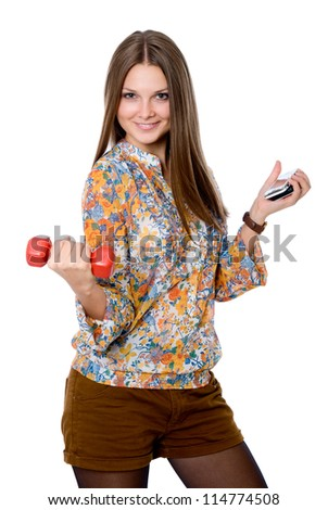 Portrait of a smiling young woman with dumbbell in one hand and cell phone in the other. isolated on white, studio shot