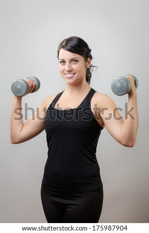 Portrait of a smiling young woman with dumbbell shot in the studio