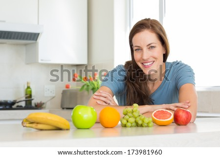 Portrait of a smiling young woman with fruits on counter in the kitchen at home