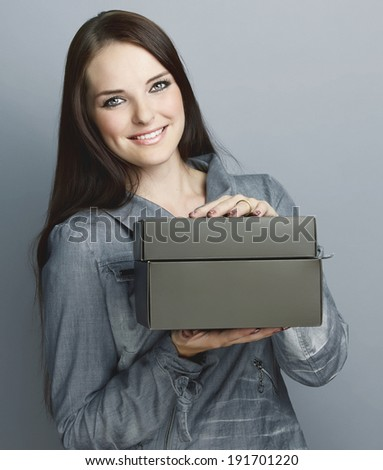 Portrait of a smiling young woman, with long brunette hair, on gray studio background, holding a black paper box with space for text  - stock photo