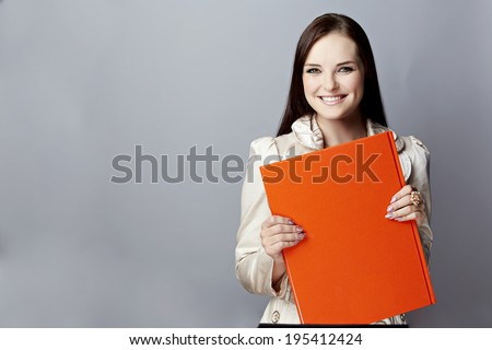 Portrait of a smiling young woman, with long brunette hair, on gray studio background, holding a closed red book or album in her hands - stock photo