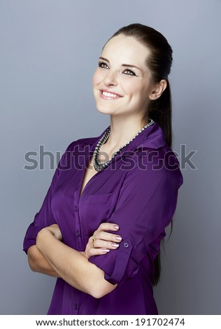 Portrait of a smiling young woman, with long brunette hair, on gray studio background, wearing purple shirt and luxury statement necklace - stock photo