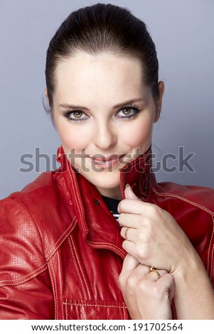 Portrait of a smiling young woman, with long brunette hair, on gray studio background, wearing leather red luxury jacket  - stock photo