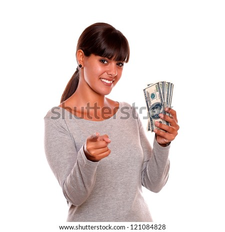 Portrait of a smiling young woman with money looking and pointing at you standing over white background - stock photo