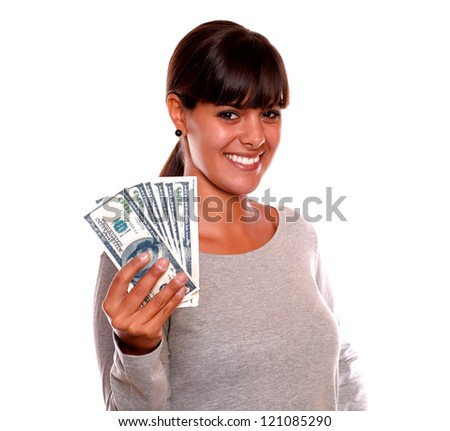 Portrait of a smiling young woman with money looking at you standing over white background - stock photo