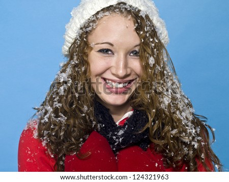 Portrait of a smiling young woman with snow on her hair