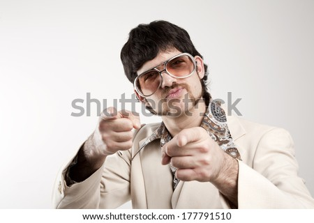 Portrait of a smug retro man in a 1970s leisure suit and sunglasses pointing to the camera  - stock photo