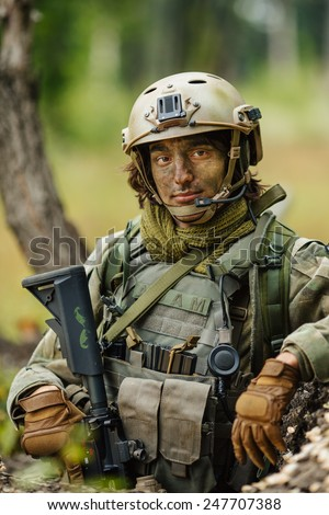 Portrait of a soldier in the woods with a gun