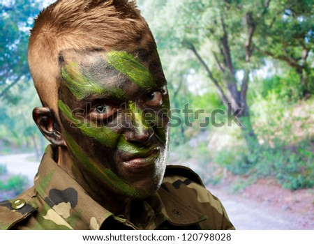 portrait of a soldier with camouflage painting at a park