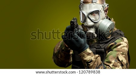 Portrait Of A Soldier With Gas Mask Aiming With Gun against a dark green background