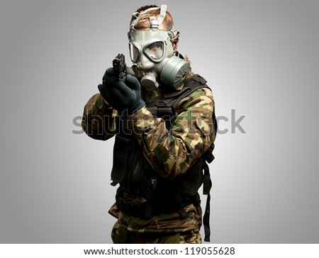 Portrait Of A Soldier With Gas Mask Aiming With Gun against a grey background - stock photo