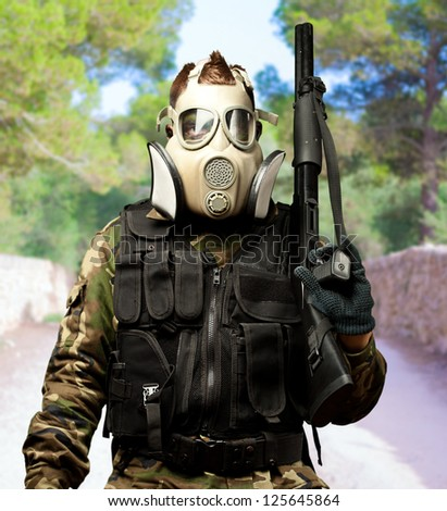 Portrait Of A Soldier With Gas Mask at a park - stock photo