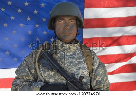 Portrait of a soldier with gun standing in front of American flag