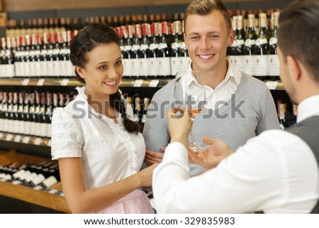 Portrait of a sommelier carrying out a wine tasting in a specialized store to a couple, standing smiling and looking at the glass of white whine