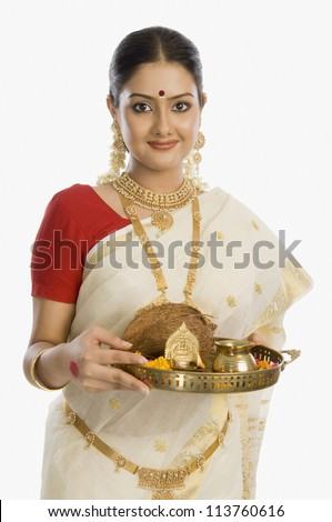 Portrait of a South Indian woman holding a plate of religious offerings