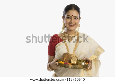 Portrait of a South Indian woman holding a plate of religious offerings - stock photo