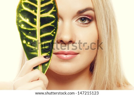 Portrait of a spa woman. Beautiful blonde girl after bath hides a half of her face with a leaf of plant. Perfect skin. Skincare. Young skin. Close up. Studio shot