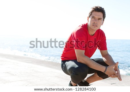 Portrait of a sports man crouching down on a track by the sea on a sunny day, being thoughtful against a blue sky. - stock photo