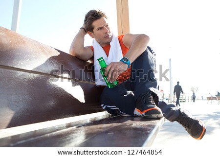Portrait of a sports man relaxing sitting down on a wooden bench and holding a bottle of water, against a sunny blue sky. - stock photo